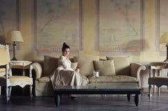 Het ontspannen van de vrouw in de bank royalty-vrije stock afbeelding