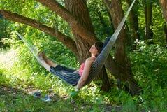 Het ontspannen van de vrouw in de hangmat Royalty-vrije Stock Afbeeldingen