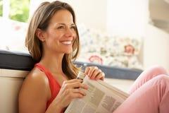 Het Ontspannen van de vrouw met Krant thuis Stock Foto's