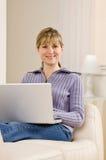 Het ontspannen van de vrouw op bank in woonkamer Stock Afbeeldingen