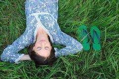 Het ontspannen van de vrouw op gras stock foto