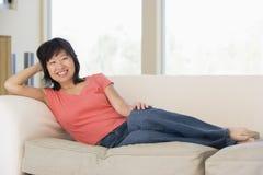Het ontspannen van de vrouw in woonkamer het glimlachen Stock Fotografie