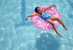 Het ontspannen van het kind bij de pool Stock Afbeeldingen