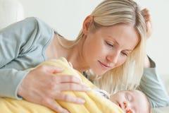 Het ontspannen van het mamma naast haar slaapbaby stock afbeeldingen