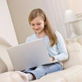 Het ontspannen van het meisje op bank in woonkamer Stock Foto's