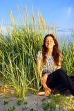Het ontspannen van het meisje op de duinen Stock Fotografie
