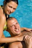 Het ontspannen van het paar door de pool Stock Afbeelding