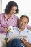 Het ontspannen van het paar met krant het glimlachen Stock Afbeelding