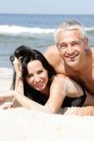 Het ontspannen van het paar op het strand Stock Foto's