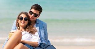 Het ontspannen van jonge zitting op het zand bij het strand met exemplaarruimte royalty-vrije stock afbeeldingen