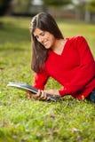 Het Ontspannen van studentenreading book while op Gras bij royalty-vrije stock afbeeldingen