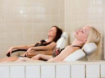 Het ontspannen van twee Vrouw bij de Pool van het Kuuroord Stock Foto's