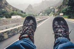 Het ontspannen voeten met trekkingsschoeisel het hangen van bestelwagenauto na lange trek manier Santo Antao-eiland, Kaapverdië stock afbeeldingen