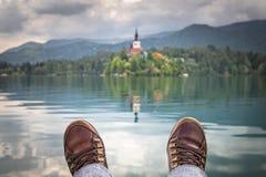 Het ontspannen voeten voor meer tapten, eiland met kerk af, bij bestemming, Slovenië, reisconcept is aangekomen royalty-vrije stock afbeelding