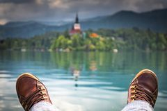 Het ontspannen voeten voor meer tapten, eiland met kerk af, die bij bestemming, Slovenië, reisconcept is aangekomen stock afbeelding