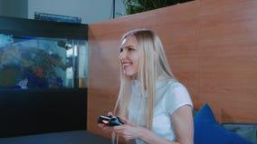 Het ontspannen vrouw het spelen console binnen Het jonge toevallige vrouw koelen op bank en het spelen videospelletje met gamepad stock videobeelden