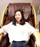 Het ontspannen vrouwenmeisje liggen op Elektrische automatische massagestoel, geniet van haar vrije comfortabele tijd royalty-vrije stock afbeeldingen