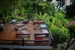 Het ontspannen wildernisterras met ligstoelen en lijsten hoog boven het overzees Stock Fotografie
