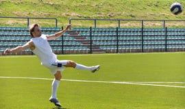 Het ontspruiten van de voetballer bal Stock Foto