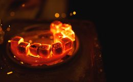 Het ontsteken van vierkante steenkool voor een waterpijp op een speciale oven met een hete spiraal royalty-vrije stock afbeelding
