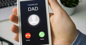Het ontvangen van telefoongesprek van Papa en het goedkeuren Mobiel communicatiemiddel concept Het zitten bij het Bureau stock videobeelden