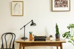 Het ontworpen trekken op een witte muur boven een antiek, houten bureau met een uitstekende, zwarte schrijfmachine in een binnenl stock afbeelding