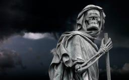 Het Onverbiddelijke Maaimachinedood verpersoonlijkte standbeeld wandelt in donkere nig Stock Foto's