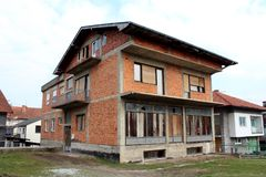 Het onvolledige rode huis in de voorsteden van de baksteenfamilie met ingescheepte voordievensters en deuren met gras en andere h royalty-vrije stock afbeeldingen
