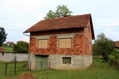 Het onvolledige verlaten rode huis van de baksteenfamilie met gesloten vensterzonneblinden en dilapidated houten garagedeuren omr stock afbeeldingen