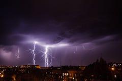 Het Onweer van de bliksem over stad stock afbeeldingen
