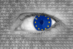 Het oog van de vrouw met vlag van E. - Europese Unie en binaire codenummers Stock Foto's