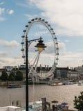 Het Oog van Londen met straatlantaarn in voorgrond en wolken op achtergrond Stock Foto