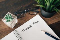 Het oogglas, de groene installatie en het notitieboekje met woord DANKEN U royalty-vrije stock fotografie