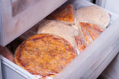 Het oogsten van pizza in de koelkast Stock Foto's