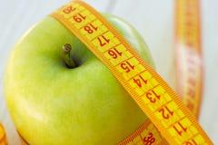 Het op dieet zijn concept Groene appel met het meten van band De groene appelen maten de meter, sportenappel royalty-vrije stock foto