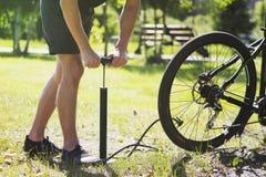 Het opblazen van de band van een fiets De fietser herstelt fiets in het forestInflating van de band van een fiets De fietser hers Stock Afbeeldingen