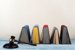 Het open boek van het wetsconcept met houten rechtershamer op lijst in een een rechtszaal of bureau van de wetshandhaving, beige  stock foto's