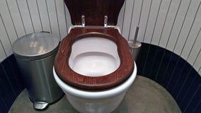 Het openbare toilet wordt schoongemaakt met een houten toiletzetel royalty-vrije stock fotografie
