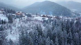 Het openbaren van antenne van gewoonde in plaats in de bergen op de winter De gebouwen van het bergdorp op sneeuwheuvelhellingen stock videobeelden