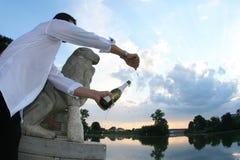 Het openen van de bruidegom champagnefles Stock Afbeeldingen