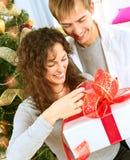 Het Openen van het paar de Gift van Kerstmis Stock Foto's