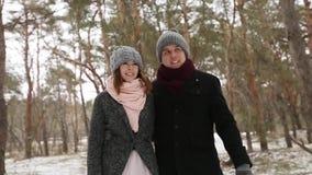 Het openlucht de winter bosschot van jong huwelijkspaar die en pretholding lopen hebben dient de pijnboombos in van het sneeuwwee stock footage