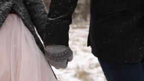 Het openlucht de winter bosschot van jong huwelijkspaar die en pretholding lopen hebben dient de pijnboombos in van het sneeuwwee stock video
