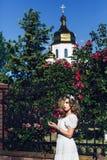 Het openluchtportret van jong mooi krullend meisje smeedde dichtbij rooster met rozen stock foto