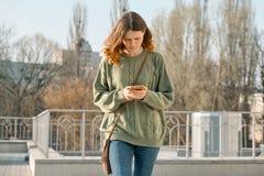Het openluchtportret van het mooie tienermeisje lopen en het texting op mobiele telefoon, springt zonnige dagachtergrond op stock afbeeldingen