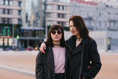 Het openluchtportret van twee modieuze en mooie meisjes kleedde meisjes op de achtergrond van de stad Royalty-vrije Stock Fotografie