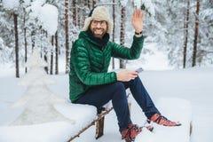 Het openluchtschot van glimlachend mannetje draagt bril gekleed in warme kleren, zit de golven met hand zoals opmerkt iemand, sma royalty-vrije stock afbeelding