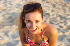 Het openluchtschot van glimlachende jonge vrouw in bikini die zich op bevinden is royalty-vrije stock afbeelding
