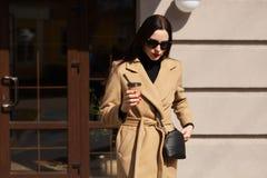 Het openluchtschot van mooie elegante vrouw die beige laag en zwarte suglasses dragen, gaat langs straat terwijl het drinken van  stock foto's