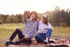 Het openluchtschot van tevreden meisje en de vriend hebben vreugde samen, zitten op plaid, stellen voor het maken van foto's in s stock afbeelding